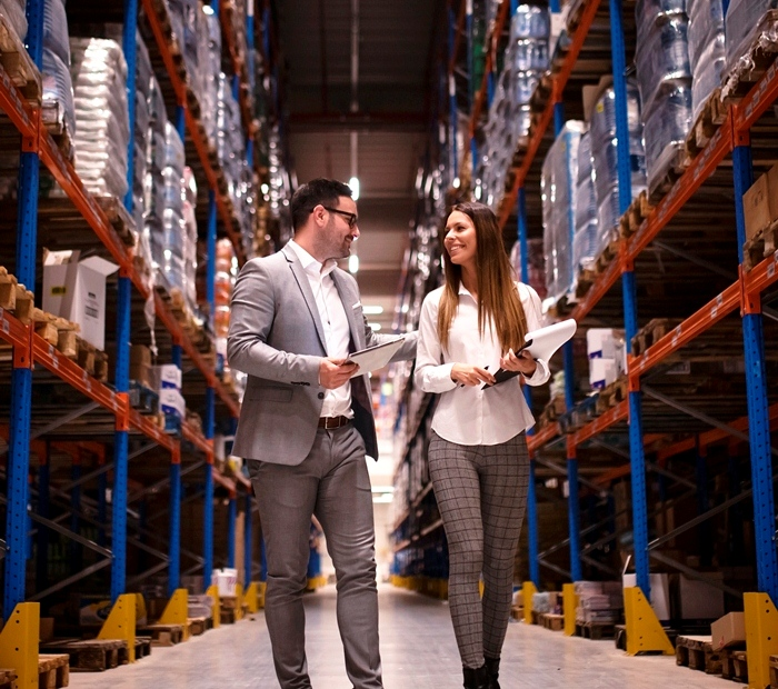 Business people walking through large distribution center and talking about increasing production and organization.